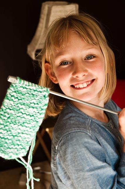 A child proudly holding a knitting needle with her first strip of knitting on it