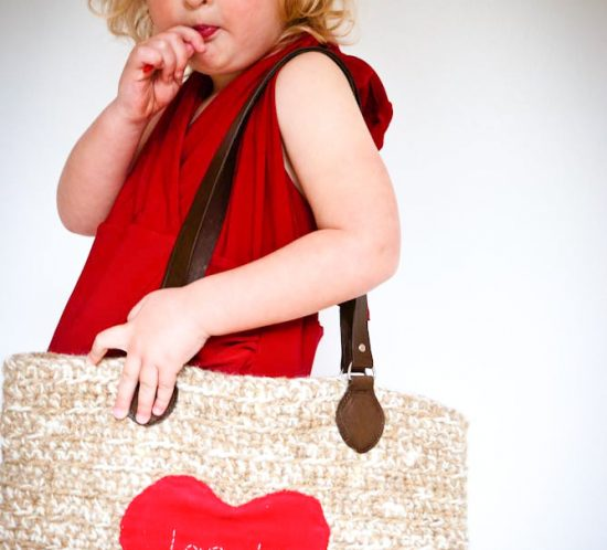 Young girl carring an oversize crochet handbag
