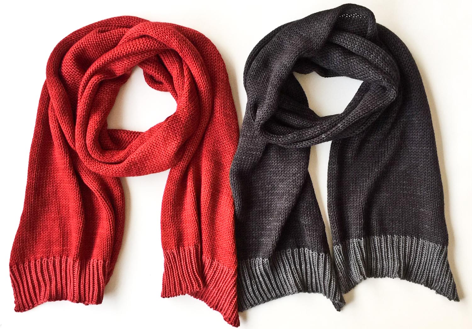 Two hand knit wool scarves in Cowgirlblues Merino DK yarn colours Chilli Pepper and Charcoal