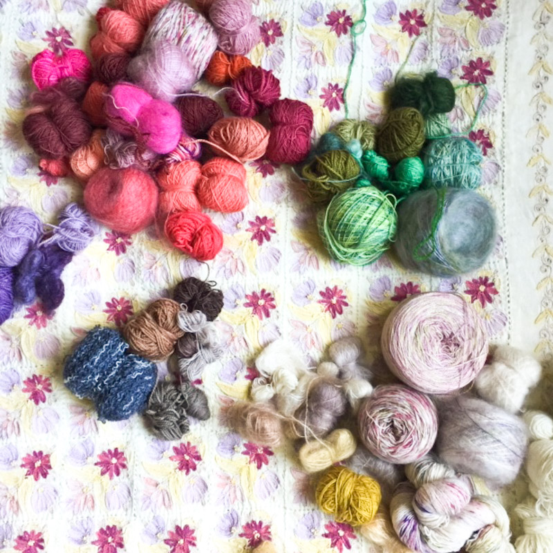 Collection of Cowgirlblues yarns in different colours on a patterned background