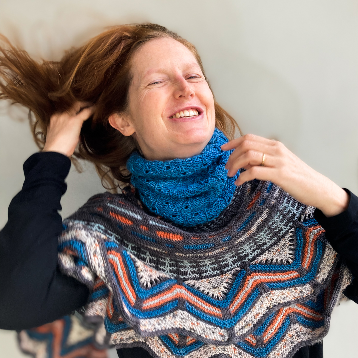 Bridget Henderson tosses her hair back wearing the Wild Weather Neckwarmer knit in Cowgirlblues Merino DK colour Guinea Fowl, and the Slipstravaganza Shawl knit in Cowgirlblues Merino Twist.