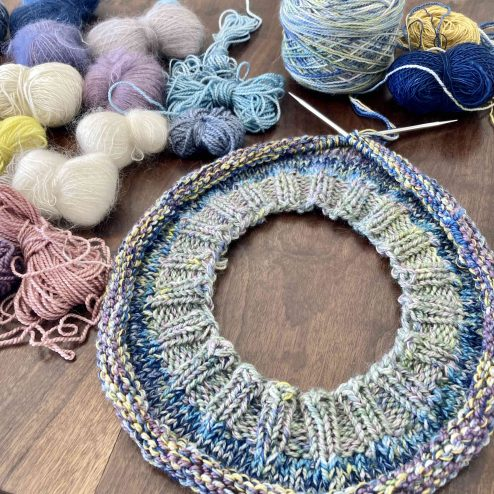 Circular knitting needles on a wooden table surrounded by small yarn ends, the knitting on the needle is in pale green and blue with a ribbed cast-on edge