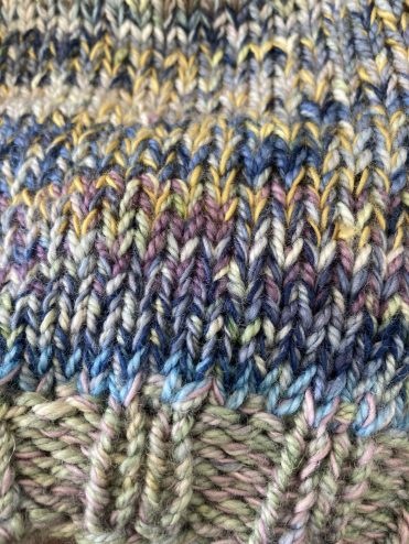 Close up of a knit showing how to change the colour with a combination of marled yarns and colours including pale green, light blue, indigo, purple and mustard
